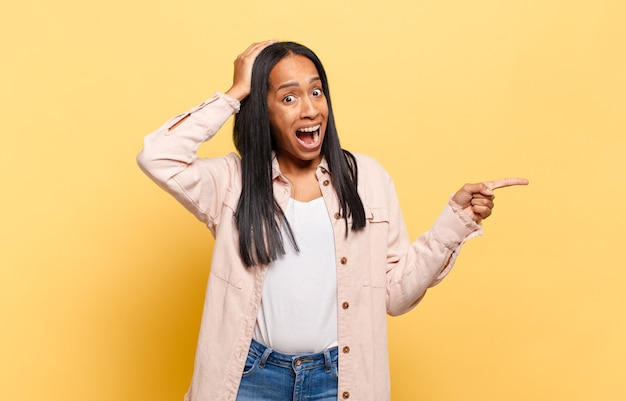 Jonge zwarte vrouw lacht, ziet er gelukkig, positief en verrast uit en realiseert zich een geweldig idee dat naar de laterale kopieerruimte wijst