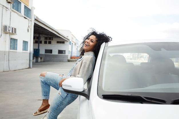 Jonge zwarte vrouw met afro haar lachen en genieten van leunend op haar auto