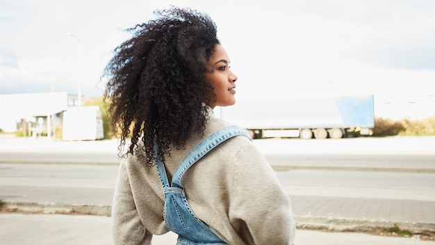 Jonge zwarte vrouw met afro haar lachen en genieten