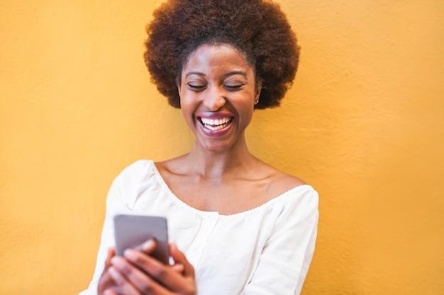 Jonge zwarte vrouw met behulp van slimme mobiele telefoon