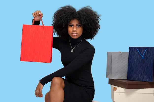 Jonge zwarte vrouw met boodschappentas meerdere dozen en boodschappentassen naast haar blauwe achtergrond
