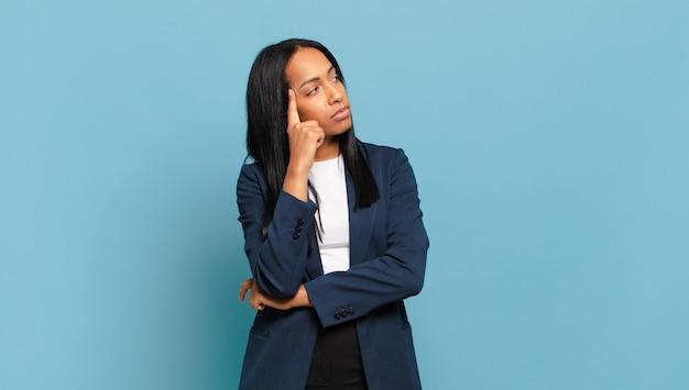 Jonge zwarte vrouw met een geconcentreerde blik, die zich afvroeg met een twijfelachtige uitdrukking, opkijkend en opzij. bedrijfsconcept