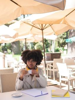 Jonge zwarte vrouw met een kopje koffie zittend op een koffiebar, buitenshuis