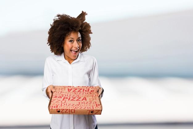 Jonge zwarte vrouw met een pizzadoos