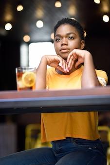 Jonge zwarte vrouw met heel kort haar dat een glas koude thee neemt.