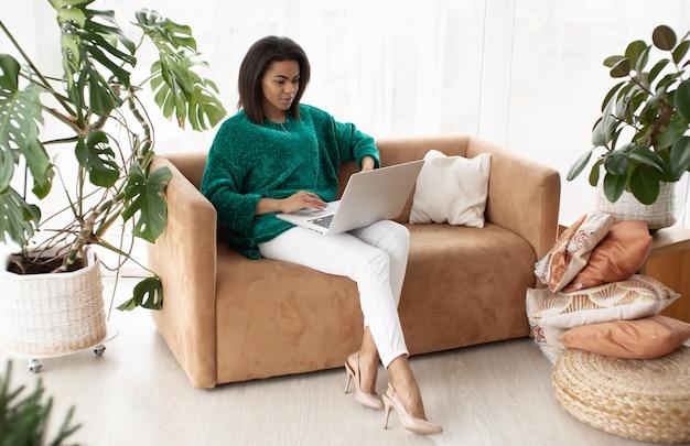 Jonge zwarte vrouw met laptopcomputer, zittend in lichte woonkamer.