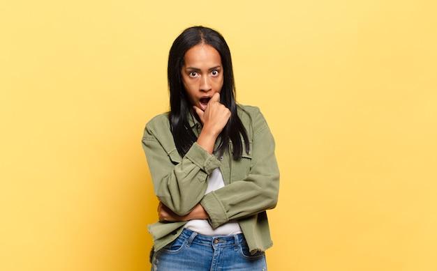 Jonge zwarte vrouw met mond en ogen wijd open en hand op kin, zich onaangenaam geschokt voelen, zeggen wat of wauw