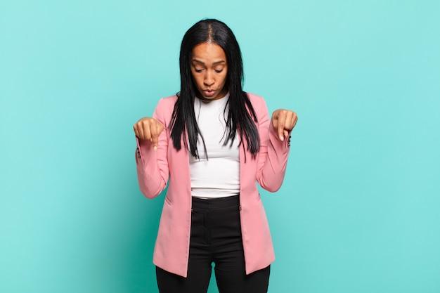 Jonge zwarte vrouw met open mond die met beide handen naar beneden wijst, geschokt, verbaasd en verrast. bedrijfsconcept