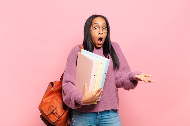 Jonge zwarte vrouw met open mond en verbaasd, geschokt en verbaasd met een ongelooflijke verrassing. studentenconcept