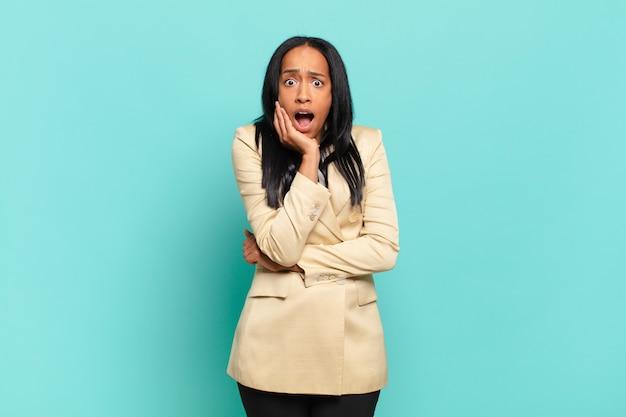 Jonge zwarte vrouw met open mond van shock en ongeloof