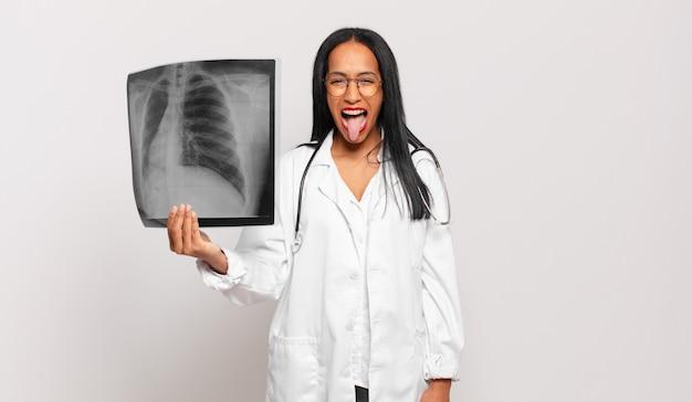 Jonge zwarte vrouw met vrolijke, zorgeloze, rebelse houding, grappen maken en tong uitsteken, plezier maken. arts concept