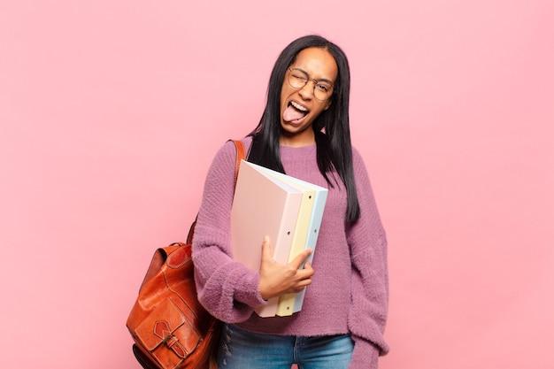 Jonge zwarte vrouw met vrolijke, zorgeloze, rebelse houding, grappen maken en tong uitsteken, plezier maken. studentenconcept