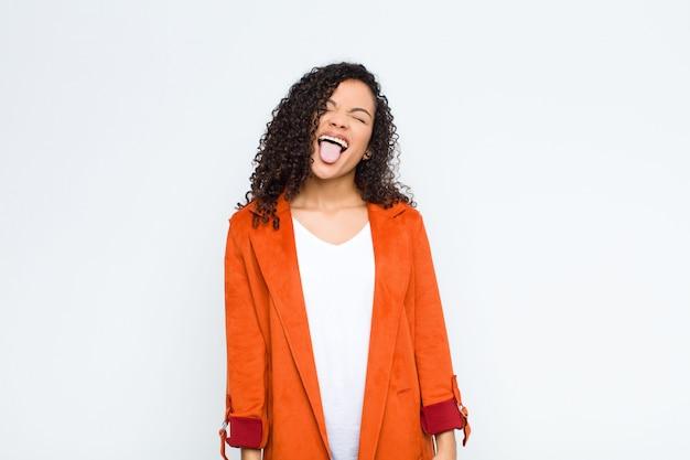 Jonge zwarte vrouw met vrolijke, zorgeloze, rebelse houding, grappen maken en tong uitsteken, plezier maken tegen witte muur