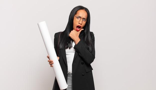 Jonge zwarte vrouw met wijd open mond en ogen en hand op kin, onaangenaam geschokt, wat zeggend of wauw. architect concept