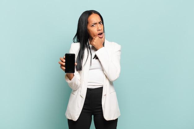 Jonge zwarte vrouw met wijd open mond en ogen en hand op kin, onaangenaam geschokt, wat zeggend of wauw. slimme telefoon concept