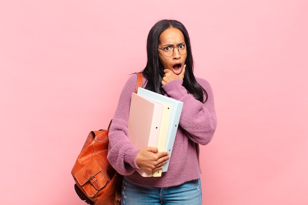 Jonge zwarte vrouw met wijd open mond en ogen en hand op kin, onaangenaam geschokt, wat zeggend of wauw. studentenconcept