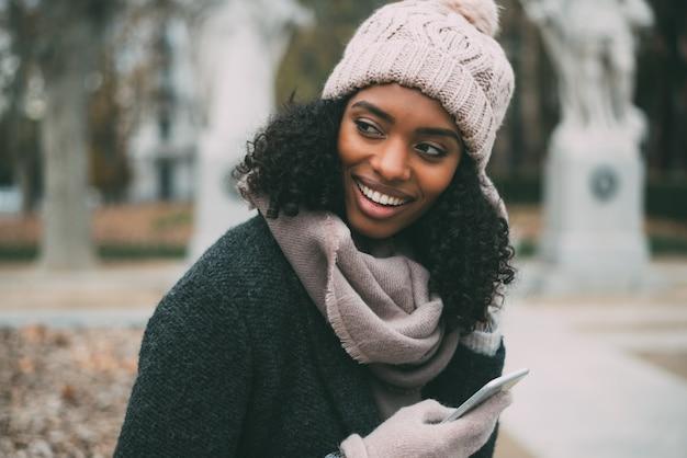 Jonge zwarte vrouw op de mobiele telefoon in de buurt van het koninklijk paleis in de winter