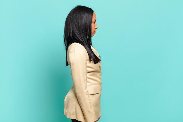 Jonge zwarte vrouw op profielweergave die ruimte vooruit wil kopiëren, denken, fantaseren of dagdromen. bedrijfsconcept
