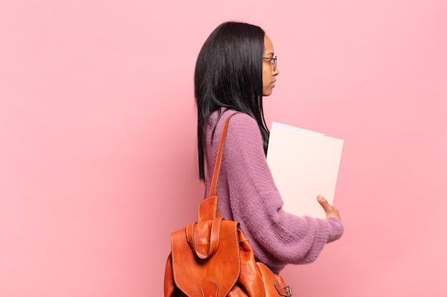 Jonge zwarte vrouw op profielweergave die ruimte vooruit wil kopiëren, denken, fantaseren of dagdromen. studentenconcept