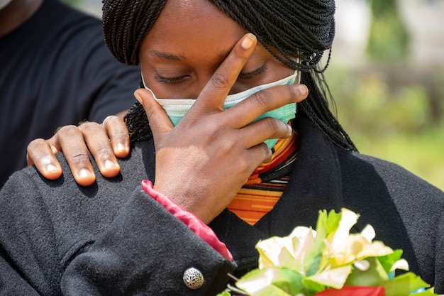 Jonge zwarte vrouw rouwt, draagt zwarte en houdt bloemen vast, iemand legt een hand op haar om te troosten
