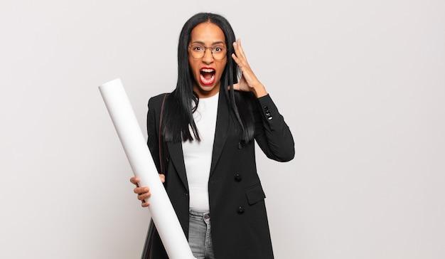 Jonge zwarte vrouw schreeuwt met de handen in de lucht, voelt zich woedend, gefrustreerd, gestrest en overstuur. architect concept