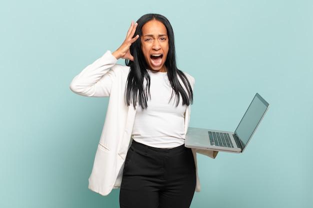 Jonge zwarte vrouw schreeuwt met de handen in de lucht, voelt zich woedend, gefrustreerd, gestrest en overstuur. laptopconcept