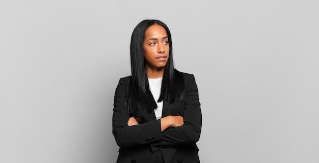 Jonge zwarte vrouw twijfelt of denkt, bijt lip en voelt zich onzeker en nerveus, op zoek naar ruimte aan de zijkant. bedrijfsconcept