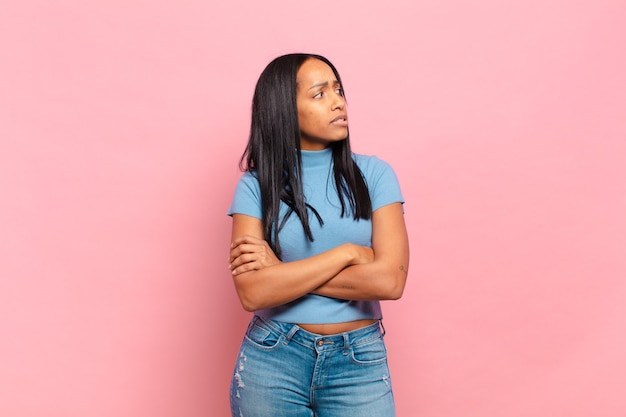 Jonge zwarte vrouw twijfelt of denkt, bijt op lip en voelt zich onzeker en nerveus, op zoek naar ruimte aan de zijkant