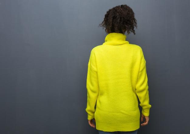 Jonge zwarte vrouw van achteren, terugkijkend