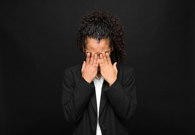 Jonge zwarte vrouw verdrietig, gefrustreerd, nerveus en depressief, kegelvormig gezicht met beide handen, huilend op zwarte muur