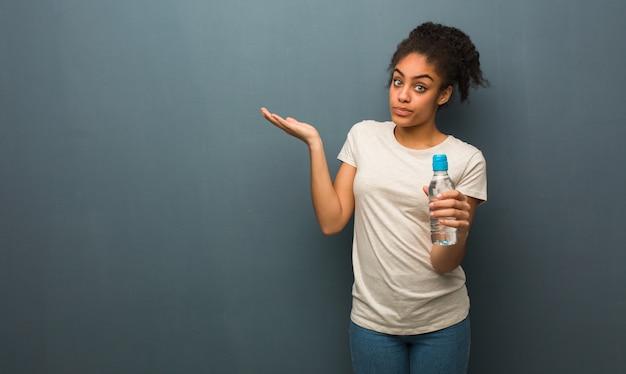 Jonge zwarte vrouw verward en twijfelachtig. ze houdt een fles water vast.