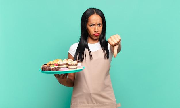 Jonge zwarte vrouw voelt zich boos, boos, geïrriteerd, teleurgesteld of ontevreden, duimen naar beneden met een serieuze blik. bakkerij chef-kok concept