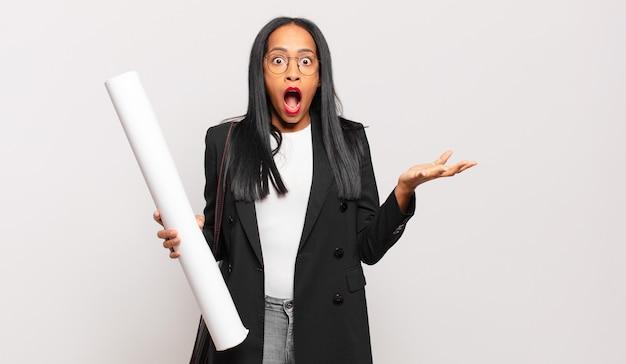 Jonge zwarte vrouw voelt zich extreem geschokt en verrast, angstig en in paniek, met een gestrest en geschokte blik. architect concept