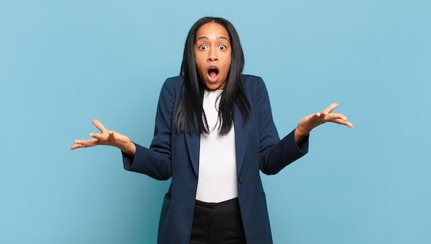 Jonge zwarte vrouw voelt zich extreem geschokt en verrast, angstig en in paniek, met een gestrest en geschokte blik. bedrijfsconcept