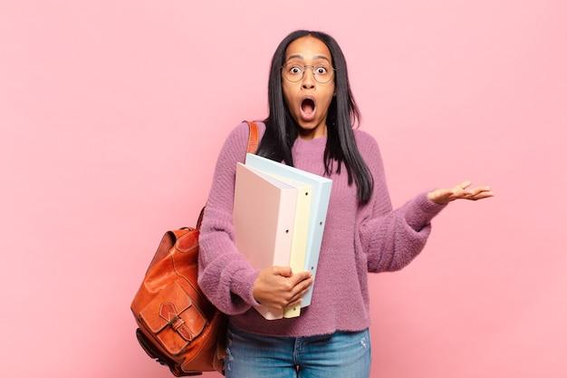 Jonge zwarte vrouw voelt zich extreem geschokt en verrast, angstig en in paniek, met een gestrest en geschokte blik. studentenconcept