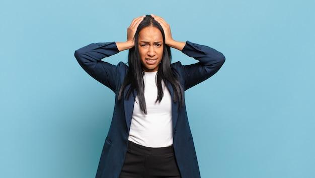 Jonge zwarte vrouw voelt zich gefrustreerd en geïrriteerd, ziek en moe van falen, beu met saaie, saaie taken. bedrijfsconcept