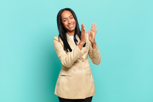 Jonge zwarte vrouw voelt zich gelukkig en succesvol, lacht en klapt in de handen en zegt gefeliciteerd met een applaus. bedrijfsconcept
