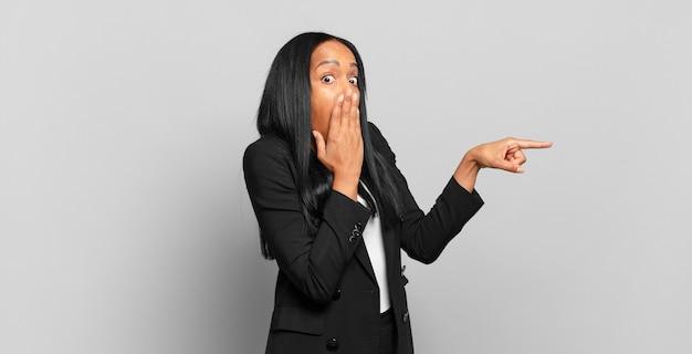 Jonge zwarte vrouw voelt zich gelukkig, geschokt en verrast, bedekt de mond met de hand en wijst naar de laterale kopieerruimte. bedrijfsconcept