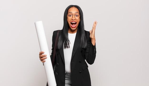 Jonge zwarte vrouw voelt zich gelukkig, opgewonden, verrast of geschokt, glimlacht en verbaasd over iets ongelooflijks. architect concept