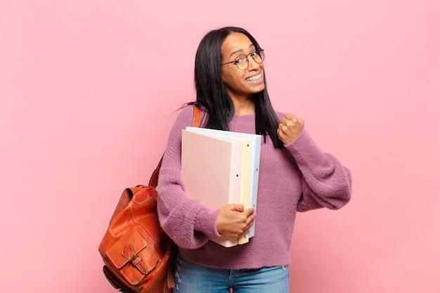 Jonge zwarte vrouw voelt zich gelukkig, positief en succesvol, gemotiveerd wanneer ze voor een uitdaging staat of goede resultaten viert. studentenconcept