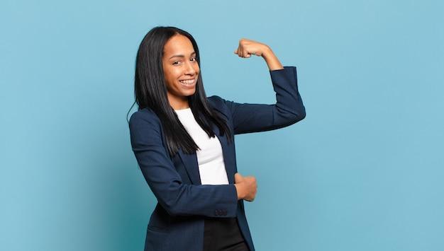 Jonge zwarte vrouw voelt zich gelukkig, tevreden en krachtig, buigt fit en gespierde biceps, ziet er sterk uit voor de sportschool. bedrijfsconcept
