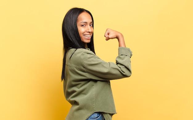 Jonge zwarte vrouw voelt zich gelukkig, tevreden en krachtig, buigt fit en gespierde biceps, ziet er sterk uit voor de sportschool
