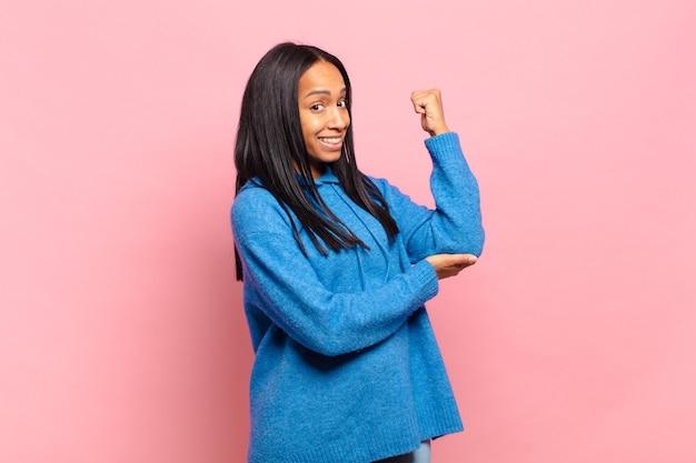 Jonge zwarte vrouw voelt zich gelukkig, tevreden en krachtig, buigt fit en gespierde biceps