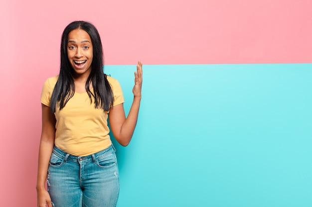 Jonge zwarte vrouw voelt zich gelukkig, verrast en opgewekt, glimlacht met een positieve houding en realiseert een oplossing of idee. kopieer ruimteconcept