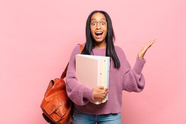 Jonge zwarte vrouw voelt zich gelukkig, verrast en opgewekt, glimlacht met een positieve houding en realiseert een oplossing of idee. studentenconcept