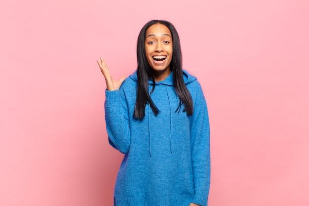 Jonge zwarte vrouw voelt zich gelukkig, verrast en opgewekt, glimlacht met een positieve houding, realiseert een oplossing of idee