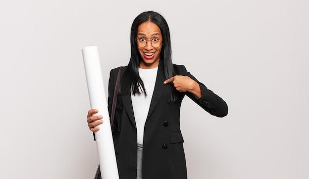 Jonge zwarte vrouw voelt zich gelukkig, verrast en trots, wijzend naar zichzelf met een opgewonden, verbaasde blik. architect concept