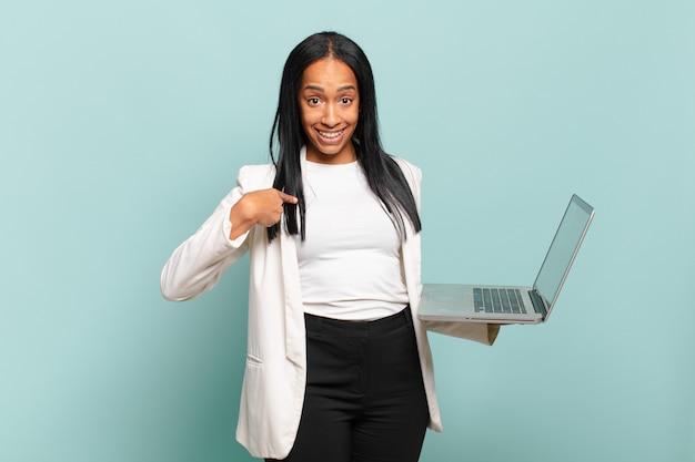 Jonge zwarte vrouw voelt zich gelukkig, verrast en trots, wijzend naar zichzelf met een opgewonden, verbaasde blik. laptop