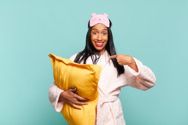 Jonge zwarte vrouw voelt zich gelukkig, verrast en trots, wijzend naar zichzelf met een opgewonden, verbaasde blik. pyjama concept