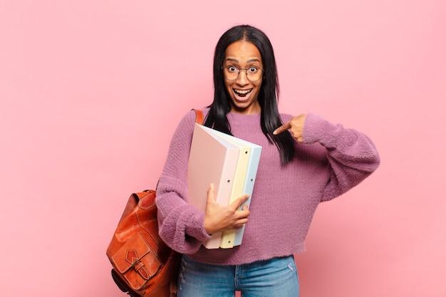 Jonge zwarte vrouw voelt zich gelukkig, verrast en trots, wijzend naar zichzelf met een opgewonden, verbaasde blik. studentenconcept